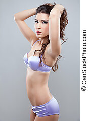 Woman posing in lingerie - Young woman with curly hair...