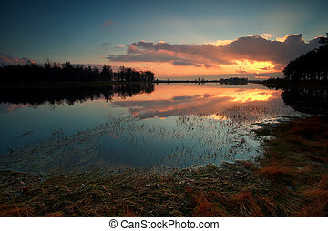 sunset on wild lake in forest