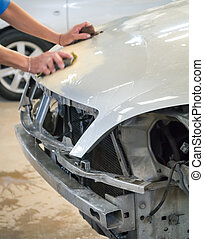 Car body repair - Worker hand sanding the car body to be...