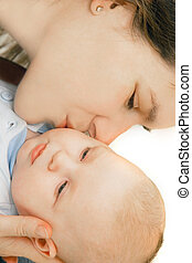 mother kissing her baby over white