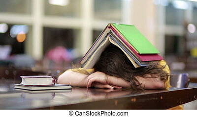 Girl buried under book stack - Girl asleep buried under book...