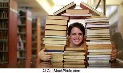 Girl gazing through books - Female student gazing through...