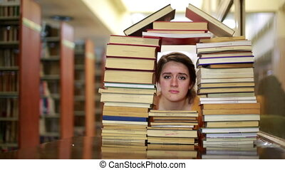 Girl gazing through books - Sad, female student gazing...