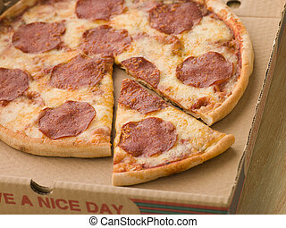 Pepperoni Pizza in a Take Away Box with a Cut Slice