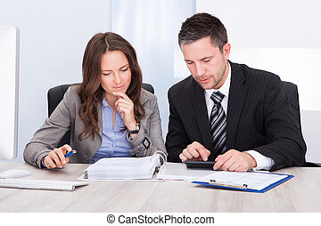 Businesspeople Calculating Finance - Two Young...