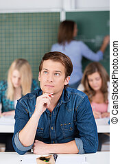 Young man in class trying to find a solution sitting at his...