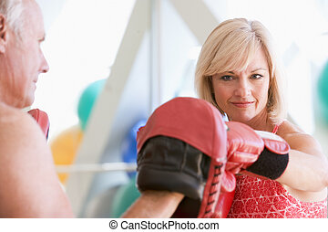 Woman Boxing With Personal Trainer At Gym