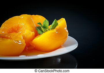 canned peaches - canned peach halves on a black background