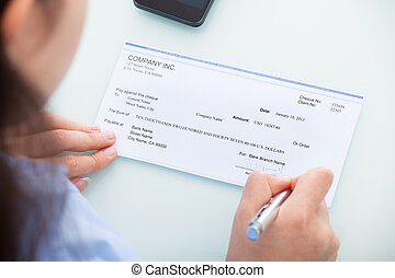Businesswoman Signing On Cheque - Close-up Of A...