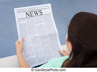 Woman Reading Newspaper - Rear View Of A Woman Sitting On...