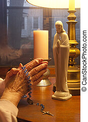 Praying The Rosary - Elderly hands praying with Rosary Beads
