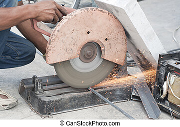 Worker cutting steel bars.