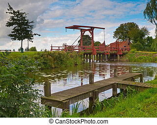 Old Wooden Drawbridge over a River in European Countryside...