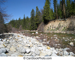 Yosemite River with Bolders on one side and green pines on...