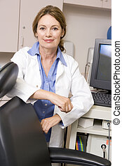 A Doctor Standing By A Computer Monitor