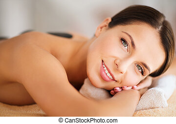 beautiful woman in spa salon with hot stones - health and...