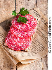 Crisp bread with salami on a sheet of newspaper