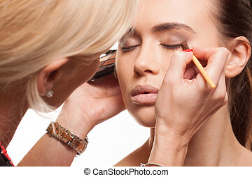 Beauty stylist applying make-up to a young model - Beauty...