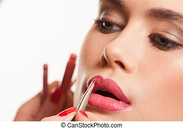 Young woman having lip gloss applied - Beautiful young woman...