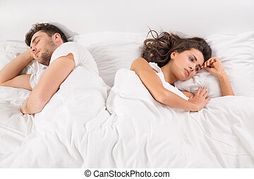Upset couple lying side by side in bed - Upset young couple...