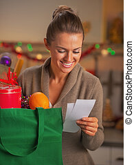 Happy young housewife looking on checks after christmas shopping