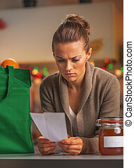 Concerned young housewife looking on checks after christmas shopping