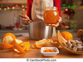 Closeup on young housewife making orange jam in christmas...