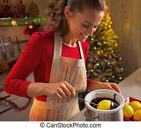 Happy young housewife making apple in chocolate glaze in...