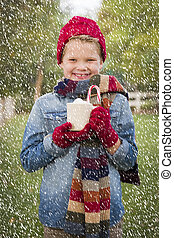 Young Boy in Warm Clothing Holding Hot Cocoa Mug Outside