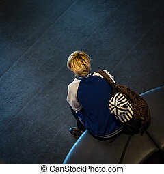 Alone teenage - Backview of lonely teenage boy sitting on...