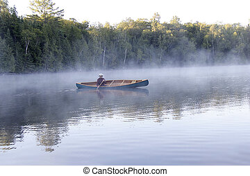Paddling Through the Mist - Man Paddling a Cedar Canoe on a...
