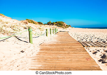 Close up view of a wood board walk in the beach pointing to...