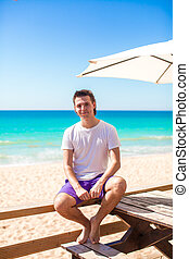 Young man on tropical beach vacation in outdoor cafe