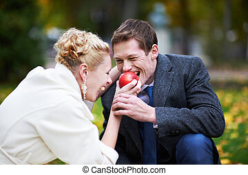 Bride feeds the groom a red apple - Bride feeds the groom a...