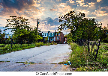 Sunset over a street and abandoned rowhouses in Baltimore,...