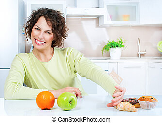 Dieting concept. Young Woman choosing between Fruits and...