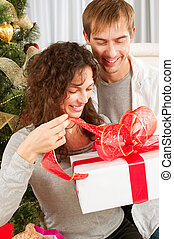 Christmas Gift. Happy Couple with Christmas and New Year Gift at Home
