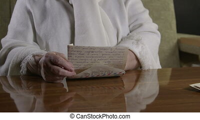 reading old letter - Senior woman raises memories reading...