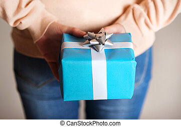 Gift box in hand - Female holding gift box with ribbon in...