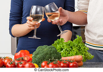 Drinking wine - Couple drinking wine and cooking together at...