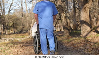 Male nurse with recovering patient in wheelchair outdoors
