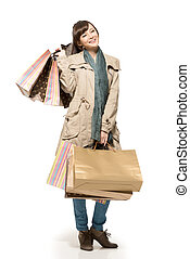Asian shopping woman holding bags, full length portrait...