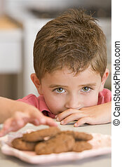 Young boy in kitchen eating cookies