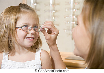 Woman trying eyeglasses on young girl at optometrists...