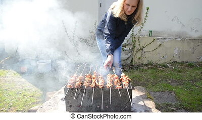 woman meat spit bake - Young blond woman bake shashlik meat...