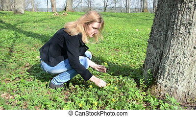 woman pick forest flowers - Blond woman in jeans and jacket...