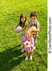Top view of kids team with sport balls - Three happy kids,...
