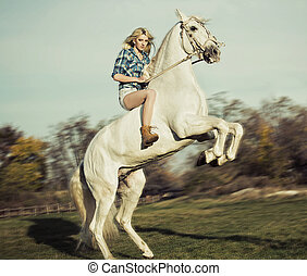 Serious blonde woman riding the horse - Serious blonde lady...
