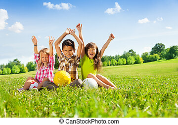 happy kids with balls and lifted hands - Portrait of three...