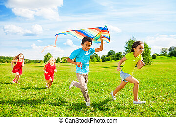 Group of kids run with kite - Group of four little kids, boy...